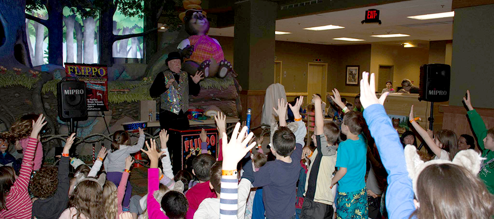 Flippo performing his act in front of a crowd of enthusiatic children