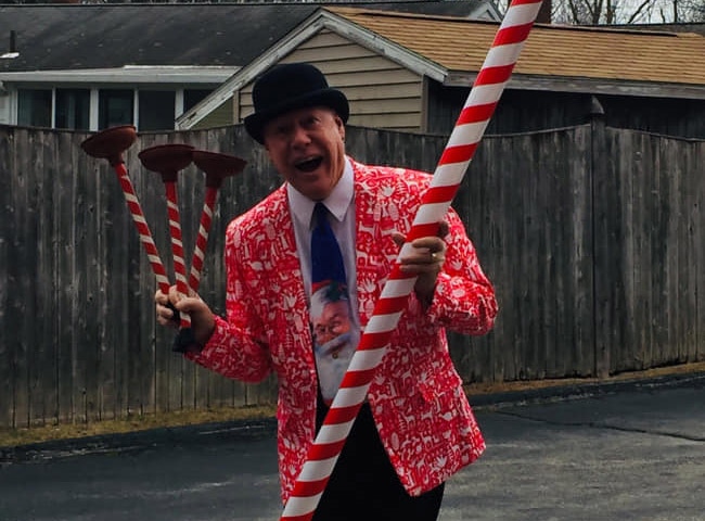 Flippo wearing a Santa themes suit and tie holding a jiant candy cane and candy cane plungers