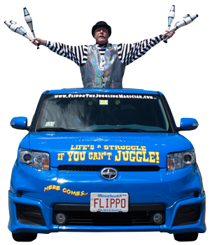Flippo standing out of the hood of his blue car with his arms spread holding bowling pins for juggling